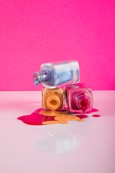 Verschütteter nagellack getrennt auf rosafarbenem hintergrund