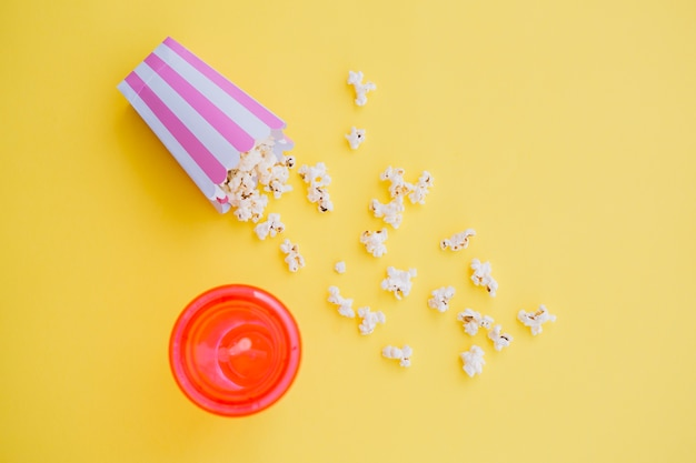 Verschüttetes popcorn in der nähe von getränkebecher