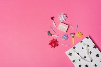 Verschüttete bunte Satinschleife; Geschenkbox; Parteigebläse und Kerzen von der Papiertüte auf rosa Hintergrund