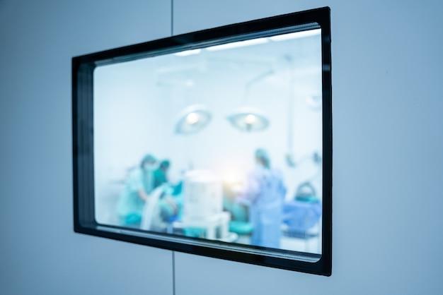 Verschwommen durch das türglas der chirurgen im operationssaal.