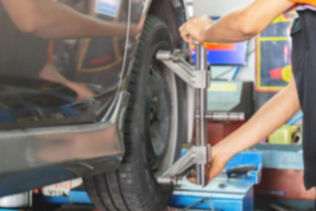 Verschwommen vom mechaniker, der die achsmessvorrichtung auf einem autorad fixiert