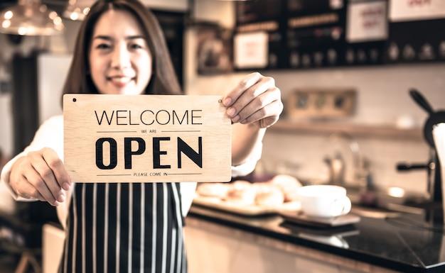Verschwommene bilder des geschäftsinhabers des coffeeshops zeigen des eröffnungsschilds und begrüßen des kunden