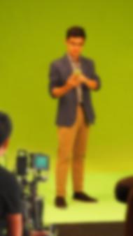 Verschwommene bilder von tv-werbefilmvideos auf großem greenscreen-hintergrund. filmteam-team, das mit schauspieler arbeitet. aufnahme mit professioneller digitalkamera und beleuchtungsset. hinter den kulissen filmen