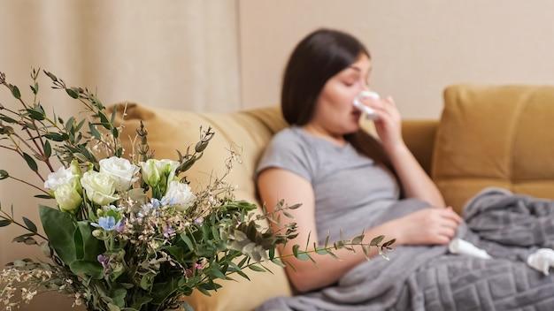 Verschwommene dame mit blumenallergie niest in papierserviette