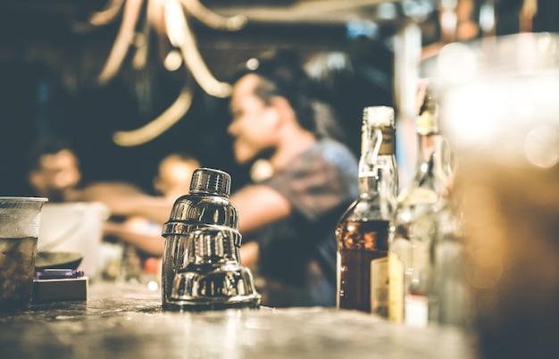 Verschwommene defokussierte seitenansicht des barmanns und der leute, die in der cocktailbar trinken und spaß haben?