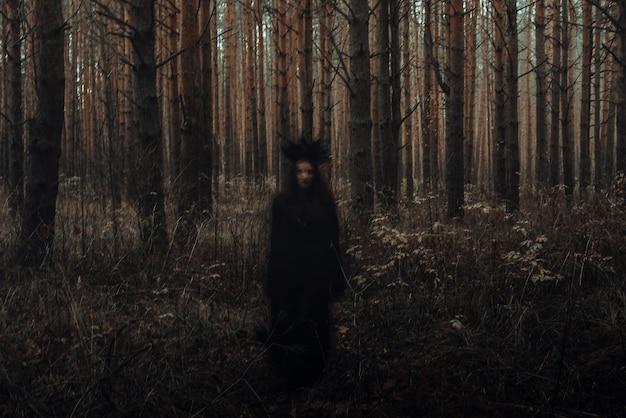 Verschwommene erschreckende schwarze silhouette einer bösen hexe, die zauber in einem dunklen wald wirkt