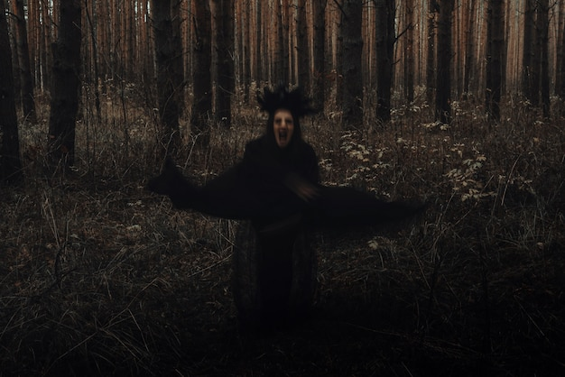 Verschwommene erschreckende schwarze silhouette einer bösen hexe in einem dunklen wald