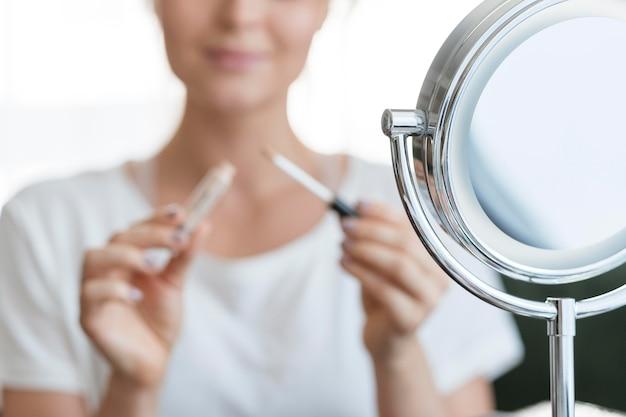 Verschwommene frau mit make-up und spiegel