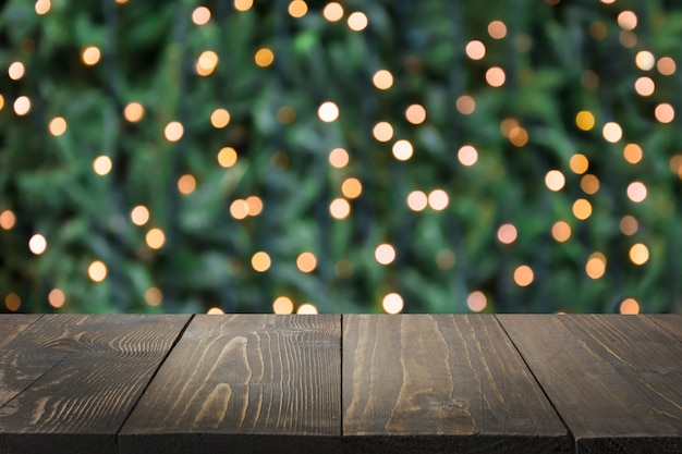 Verschwommene goldene girlande auf weihnachtsbaum als hintergrund und hölzerne tischplatte als vordergrund. weihnachtszusammenfassung. bild zur anzeige oder montage ihrer weihnachtsprodukte. speicherplatz kopieren.