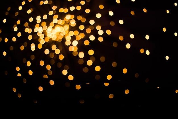 Verschwommene goldene lichter auf schwarzem hintergrund festlicher platz für text für ihr design