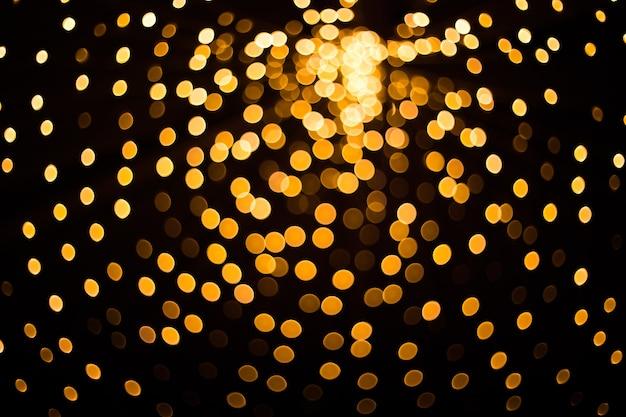 Verschwommene goldene lichter auf schwarzem hintergrund festliches muster für ihr design