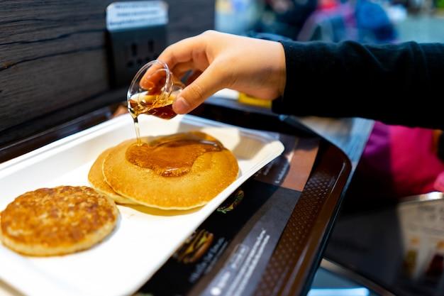 Verschwommene hand sirup auf pfannkuchen gießen. frühstückskonzept
