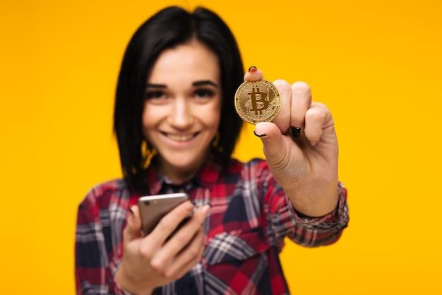 Verschwommene lächelnde frau, die ein bitcoin in der hand hält und es zeigt