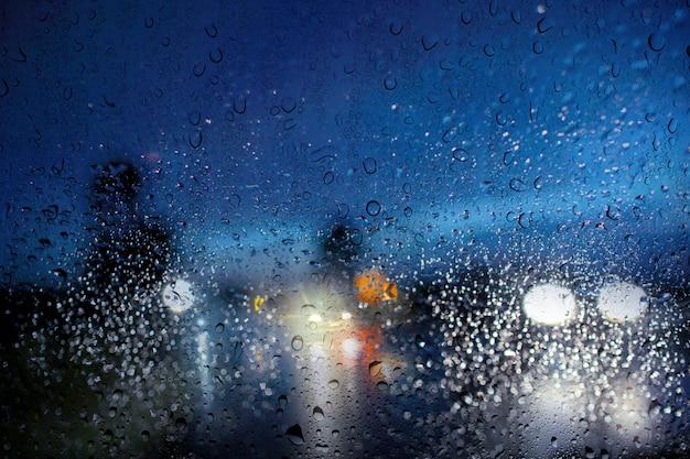 Verschwommene landstraße, blick durch den windschutz des regensturms / schlechte wetterbedingungen, unter nachtszene.