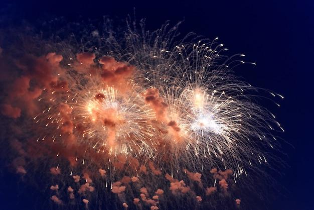 Verschwommene mehrfarbige feuerwerkslichter gegen den dunklen nachthimmel. festliches feuerwerk. lichtdefokussierung