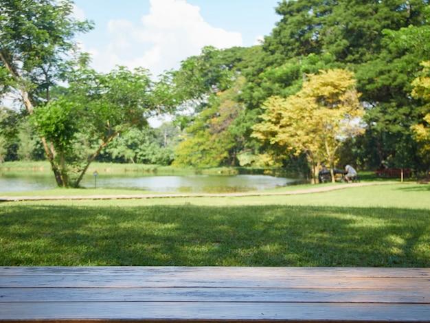 Verschwommene natur. leerer holztisch im park mit sitzenden und entspannenden personen