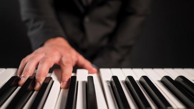 Verschwommene person, die digitales klavier spielt