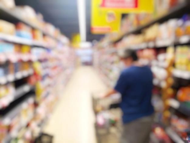 Verschwommene person, die im supermarkt einkauft