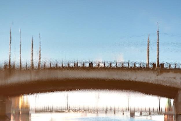 Verschwommene reflexion einer brücke auf der oberfläche eines verschmutzten städtischen flusses.