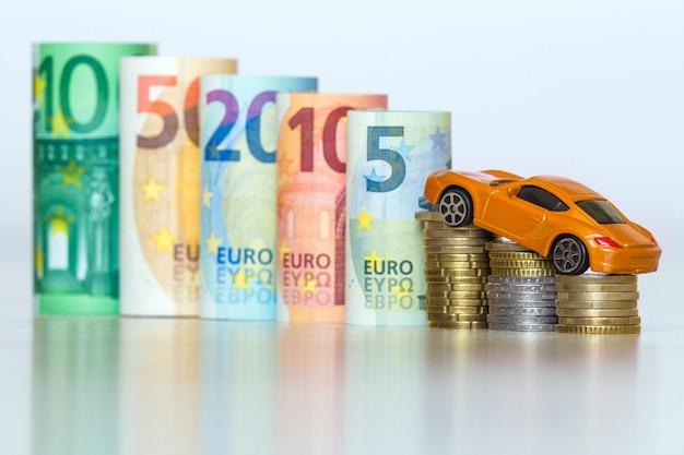 Verschwommene reihe von gerollten hundert, fünfzig, zwanzig, zehn und fünf neuen euro-banknoten und haufen münzen