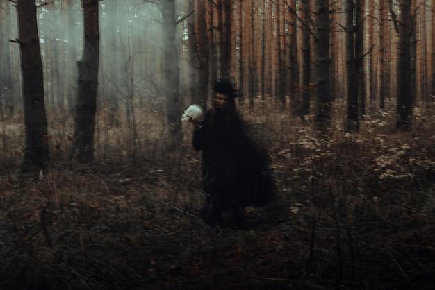 Verschwommene silhouette einer schrecklichen hexe mit einem schädel in den händen, die ein mystisches okkultes satanisches ritual in einem dunklen, düsteren wald durchführt