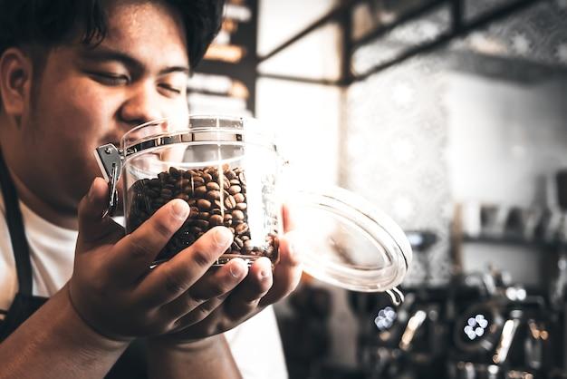 Verschwommene weiche bilder des asiatischen dicken mannes coffeeshop-besitzer riechen die hochwertigen kaffeebohnen, die in einem glasgefäß geröstet und gekocht werden, für menschen und getränkekonzept.