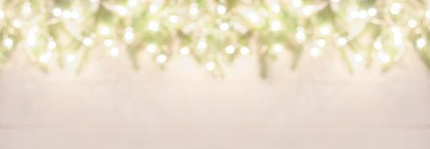 Verschwommene weihnachtsbaumzweige beleuchtet mit hellen lichtern, breiter bannerhintergrund