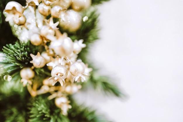 Verschwommene weihnachtsbaumzweige verziert mit goldenen blumen neujahrskomposition
