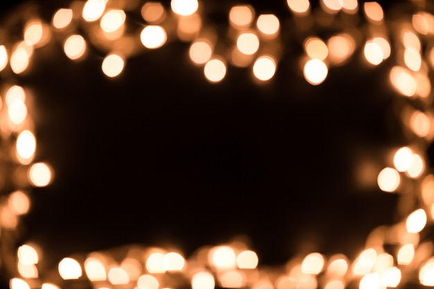 Verschwommene weihnachtsbeleuchtung. weihnachtsbeleuchtung grenze. weihnachtshintergrund mit lichtern. weihnachtslichter auf schwarzem hintergrund. neujahr.