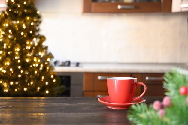 Verschwommene weihnachtsküche mit roter tasse kaffee auf hölzerner tischplatte.