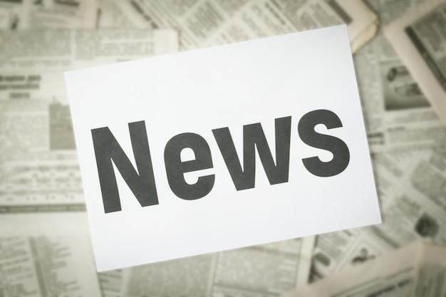 Verschwommene zeitungen auf dem tisch mit der aufschrift news auf weißem papier in der mitte