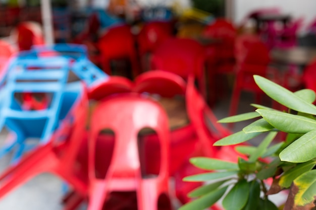 Verschwommener abstrakter hintergrund des cafés im freien. bunte tische und stühle in einem café. gelbe, blaue, rote farben. europäisches restaurant im freien in der stadt