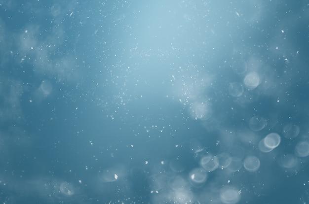 Verschwommener abstrakter hintergrund mit bokeh und schneeflocken in der luft auf blauem hintergrund