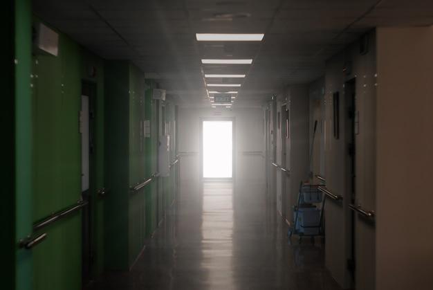 Verschwommener dunkler krankenhausflur mit einer leuchtenden tür an seinem ende eine allegorie des klinischen todes