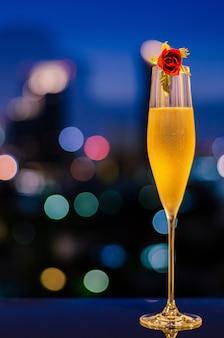 Verschwommener fokus eines glases kalten champagners mit rosenblüten auf dem tisch