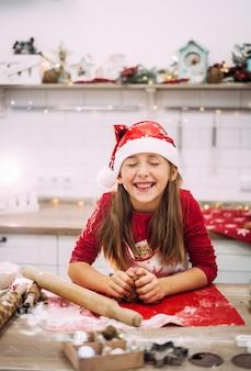 Verschwommener fokus eines teenager-mädchens, das in der küche steht und teig für lebkuchenplätzchen modelliert