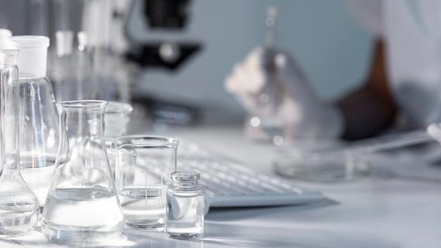 Verschwommener forscher der nahaufnahme, der glaswaren hält
