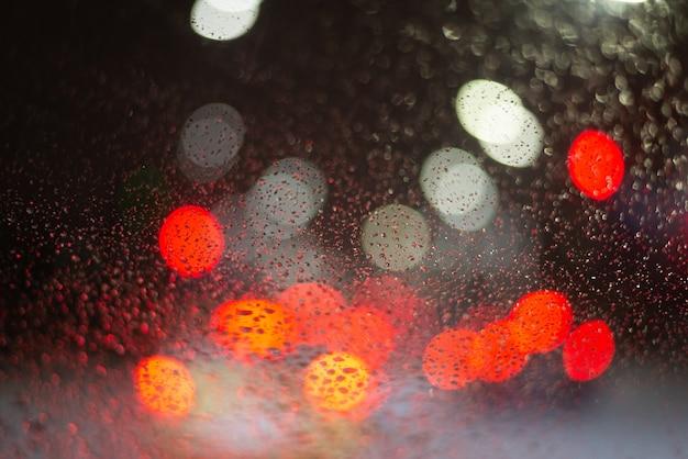 Verschwommener hintergrund mit regentropfen und lichtern.