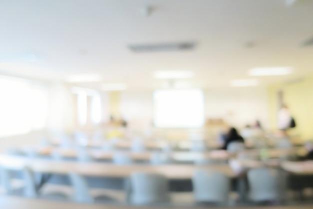 Verschwommener hörsaal oder besprechungsraum mit langem tisch, stühlen, projektor und großem fenster. bildung.