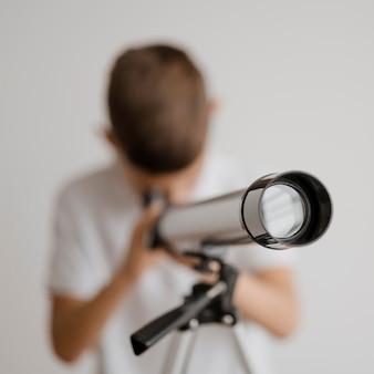 Verschwommener junge, der lernt, wie man ein teleskop benutzt