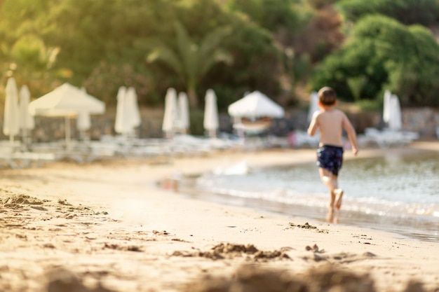 Verschwommener kleiner junge, der in den sommerferien auf dem privaten leeren strand spielt. kinder in der natur mit meer, tropischen pflanzen. glückliche kinder im urlaub am meer laufen im wasser, insel zypern