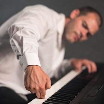 Verschwommener künstler, der verschiedene oktaven auf digitalpiano spielt