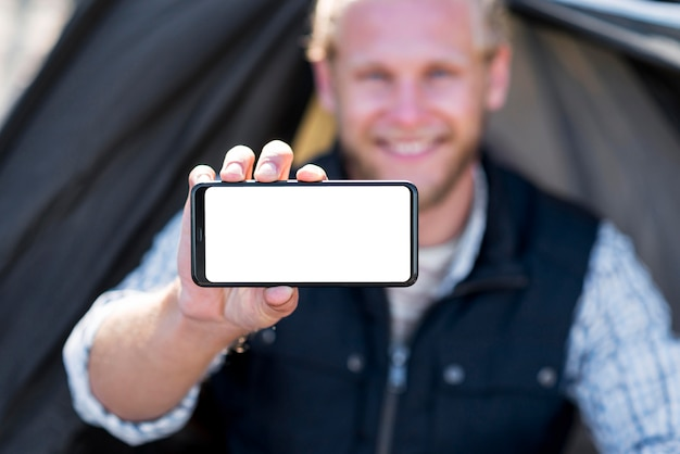 Verschwommener mann, der horizontales kopierraum-mobiltelefon hält