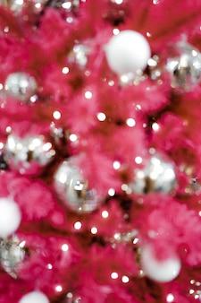 Verschwommener rosa weihnachtsbaum mit silbernen kugeln. funkelnder glitzer weihnachtsbaumschmuck