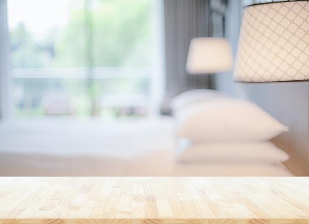 Verschwommener schlafzimmerhintergrund und hölzerne tischplatte mit anzeige für produkte