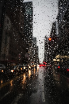 Verschwommener straßenhintergrund von new york city mit wassertropfen, lichtern und autos zur regnerischen abendzeit