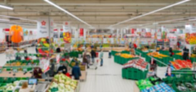 Verschwommener supermarkt. verkauf von produkten in einem einzelhandelsgeschäft. verschwommener hintergrund der käufer in einem geschäft.