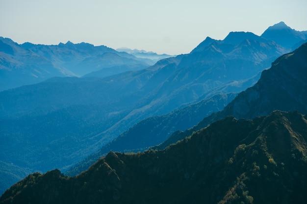 Verschwommenes abstraktes natürliches mit bergen in einem morgendlichen blauen nebel