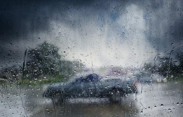 Verschwommenes auto, blick durch die windschutzscheibe des regnerischen tages. selektiver fokus und farbe getönt.