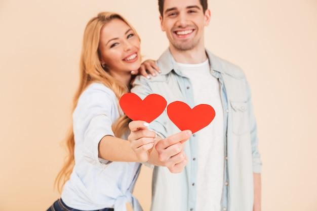 Verschwommenes foto des mannes und der frau der jungen romantischen leute in der grundkleidung, die lächelnd und rote papierherzen im fokus hält, lokalisiert über beige wand
